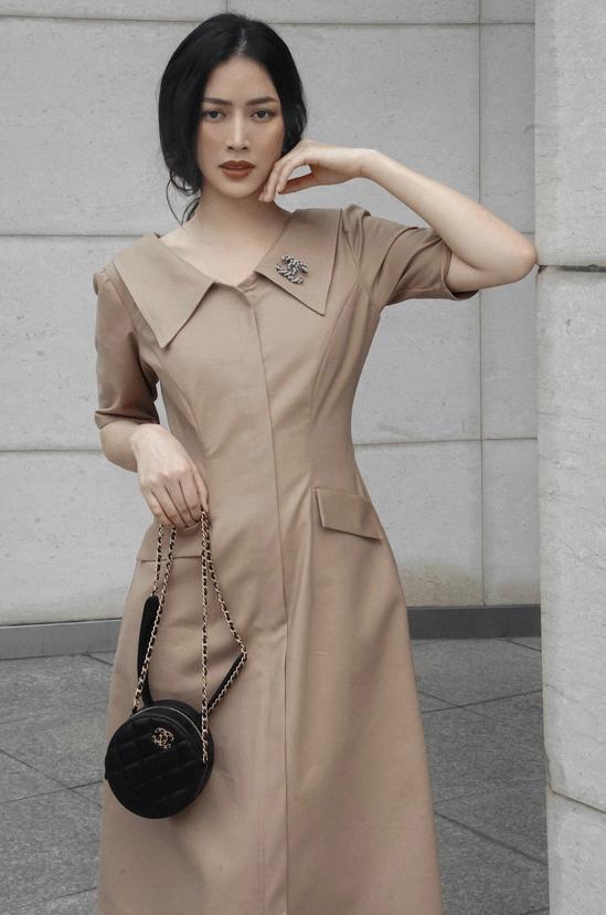 Váy liền thân mang hơi hướng cổ điển với tông màu nude đúng trend thu đông sẽ khiến người mặc sành điệu hơn khi đến văn phòng.