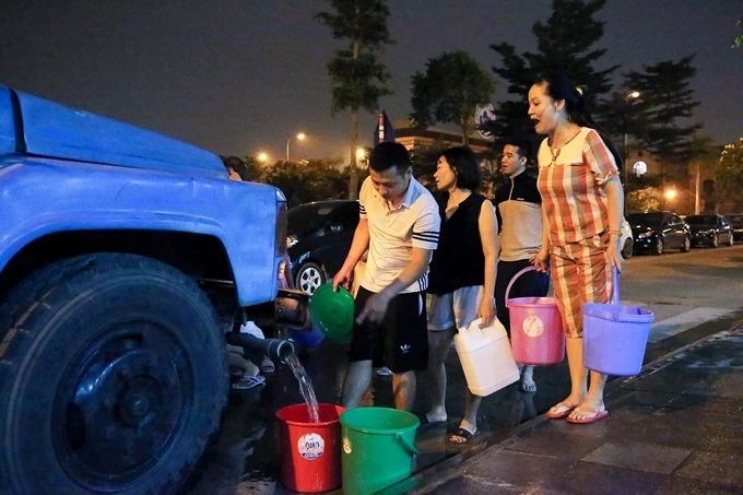 Cư dân chung cư An Khánh (Hoài Đức) xách xô để hứng nước đêm 15/10. Ảnh: Giang Huy.