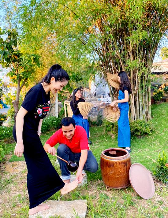 Quyền Linh múc nước trong chum rửa chân cho vợ trong khi hai cô con gái chơi đùa, tìm hiểu các dụng cụ bắt cá.