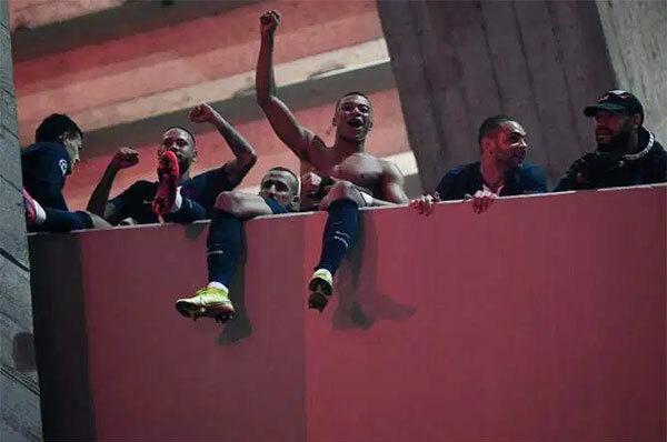 Giành vé đi tiếp, các cầu thủ PSG cởi áo chia vui với người hâm mộ bên ngoài sân Công viên các Hoàng tử - những người trước đó không được vào sân cổ vũ vì lo ngại corona virus lây lan.