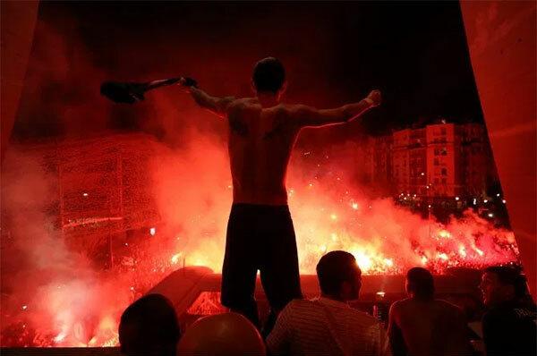 Tiền vệ Di Maria cởi áo phấn khích đứng trên ban công khi phía dưới là hàng nghìn CĐV PSG tụ tập, đốt pháo mừng suất vào tứ kết Champions League.
