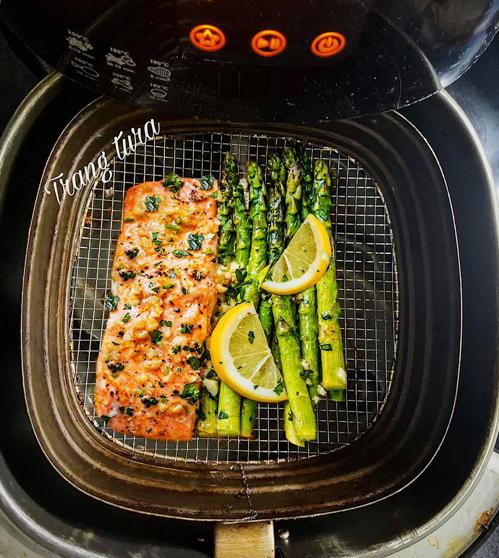 Cá hồi bỏ lò kèm măng tây:Cá hồi rửa sạch, ngâm vào sữa tươi hoặc rửa với chút rượu trắng giúp cá bớt tanh và thơm ngon hơn.Măng tây thái miếng vừa ăn. Tỏi bóc vỏ, băm nhuyễn. Chanh vàng thái lát mỏng, bào một chút vỏ để tạo mùi thơm.Bơ cắt thành miếng nhỏ.Ướp cá với chút hạt tiêu, bột nêm, bột tỏi, 5 gr bơ đã để nhiệt độ phòng cho mềm hoặc chút dầu oliu, chút lá mùi tây thái nhỏ, xát đều lên khắp miếng cá, trừ phần da cá, để trong ngăn mát tầm 30-45 phút.Xếp cá hồi vào nồi, rắc chút muối lên toàn bộ bề mặt, xếp bơ, tỏi băm lên trên. Sau đó xếp chanh vàng đã thái lát lên, măng tây xếp vào khay rồi rắc một chút vỏ chanh đã bào nhỏ để tạo mùi thơm.Nướng lần 1: 180 độ C trong 10 phút (bọc cá vào giấy bạc).Nướng lần 2: Bỏ giấy bạc ra, nướng 180 độ C trong 5 phút.Cá chín nên ăn nóng (vắt chút chanh và hạt tiêu) sẽ ngon hơn.