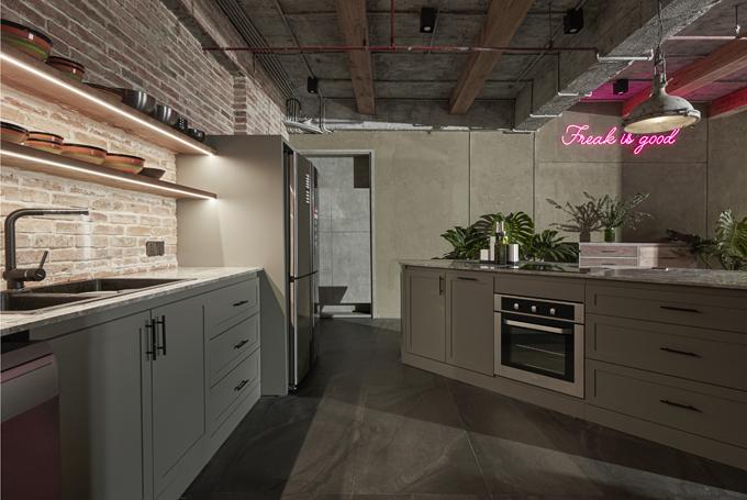 Phía tay trái là bồn rửa tay, hai kệ gắn tường để đựng bát, đĩa.