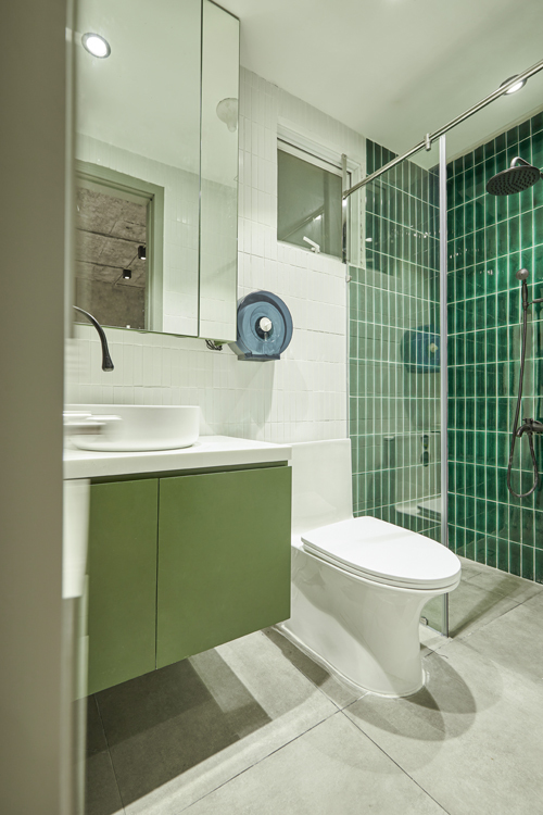 Phòng vệ sinh có tông giống phòng thử đồ, đều mang tông xanh lá.