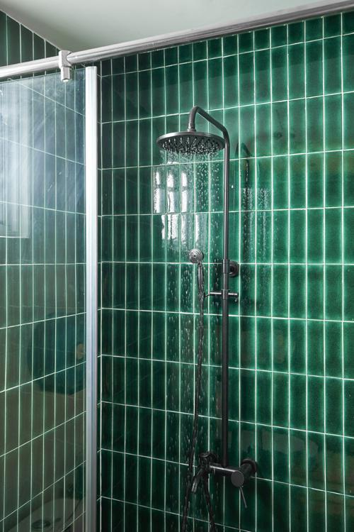 Nơi tắm đứng cách biệt bồn rửa tay bằng vách kính cường lực.