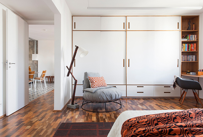 Tủ đồ quần áo liên kết với bàn trở thành phòng làm việc tại nhà, có kệ sách. Trong căn phòng này, màu sắc chủ đạo là cam đến từ giường, gối, giấy dán tường. Bảng màu ấm cùng sàn gỗ, tạo nên căn phòng ấm cúng, thoải mái.