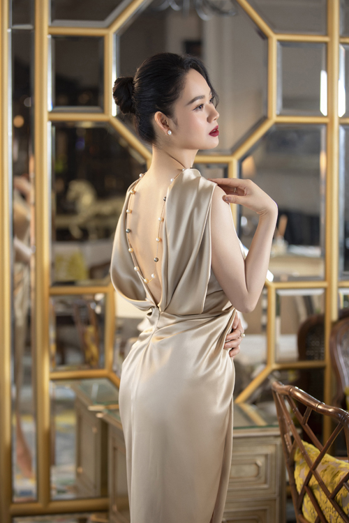 Váy lụa màu trung tính được bố trí phần hở lưng ý nhị. Trang phục khai thác vẻ sexy vừa đủ và vẫn tôn nét trang nhã cho hoa hậu.