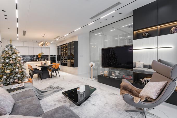 Tông màu chủ đạo của căn hộ là trắng - xám - đen đi cùng các món đồ nội thất với vật liệu gương kính bóng sáng giúp căn hộ thêm sang trọng và được mở rộng về bề ngang. Ánh sáng vàng được điểm xuyết dọc theo hệ tủ.