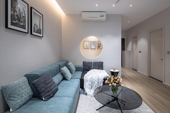 Bộ sofa chữ L gam màu xanh, xám được bố trí như một điểm nhấn của phòng khách. Chủ nhân căn hộ không cầu kỳ trong việc trang trí không gian này, chỉ bày trí đơn giản 3 bức tranh tone đen - xám - trắng trên tường.
