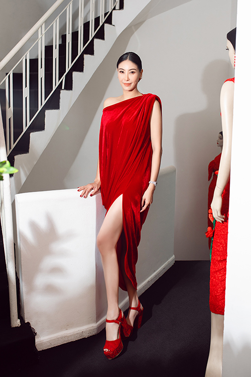 Hoa hậu Hà Kiều Anh lựa chọn mẫu váy oversize xẻ chân khoe chân dài sexy. Chất liệu nhung đỏ được xử lý khéo léo để mang lại