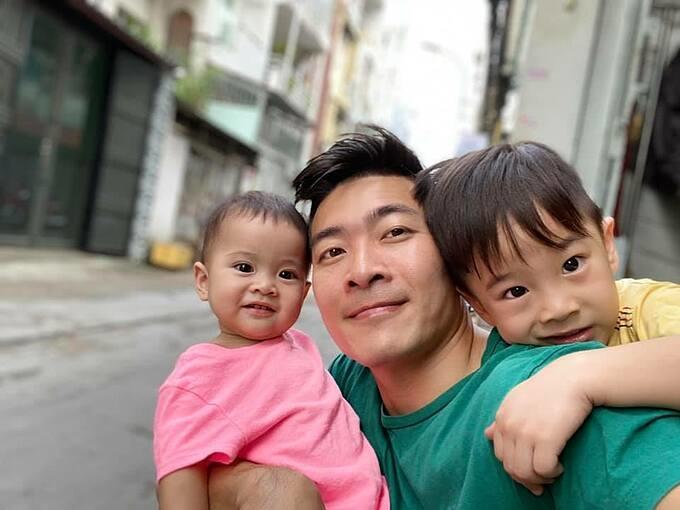 Quốc Cơ pose hình bên hai con và hỏi fan ai giống ai.