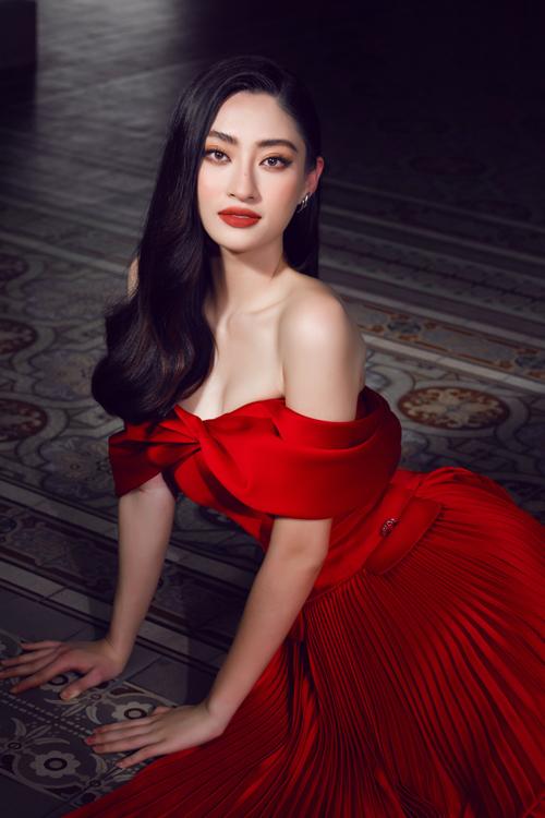 Đầm trễ vai trên tông đỏ đậm cổ điển được tăng sức hút bằng chi tiết xoắn vải cho ngực áo và phối chân váy xếp ly.