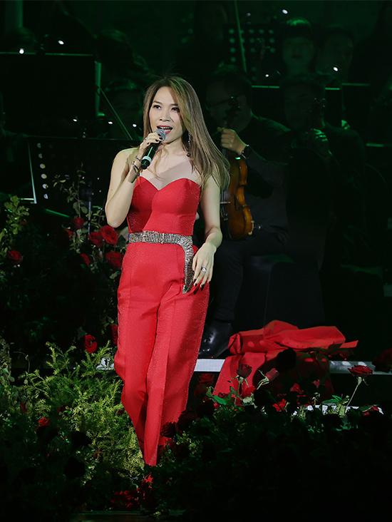 Chính vì thế, cô cởi áo khoác ngay trên sân khấu, để lộ đôi vai trần nõn nà ở tuổi 40. Thắt lưng kim loại trở thành điểm nhấn cho bộ jumpsuit màu đỏ.
