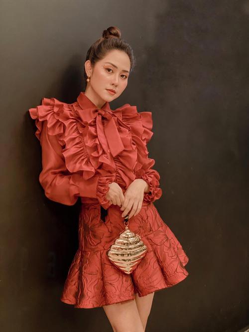 Tường Vi tôn nét điệu đà bằng áo trang trí bèo nhún kết hợp cùng chân váy thiết kế trên chất liệu vải gấm.