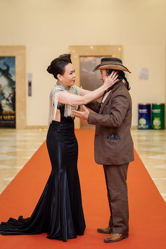 Việt Hương đến dự họp báo cùng bố chồng. Cô chỉnh trang bề ngoài cho ông khi được truyền thông đề nghị chụp ảnh chung.