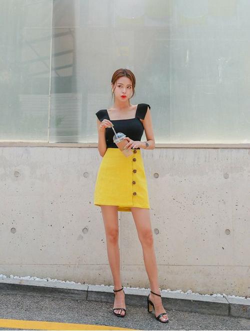 Chân váy chữ A được tô điểm thêm hàng cúc điệu đà. Ngoài sắc trắng thanh nhã thì tông vàng cũng thường được mix với trang phục đen.