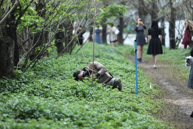 Du khách cúi sát xuống bãi cỏ để lấy góc ảnh ưng ý. Linh Nguyễn (Hội An) chia sẻ, tranh thủ ngày cuối tuần, gia đình cô chạy xe máy từ Hội An ra đây chụp hình, nhưng cảnh tượng khá đông khiến cô khó khăn lắm mới chụp được bức ảnh không dính người. Ảnh: Phú Trần.