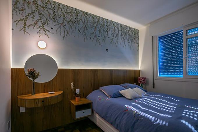 Phòng ngủ được tô điểm với tranh tường lá cây. Gia chủ chọn lựa nội thất tối giản gắn tường, không có chân tiếp xúc mặt đất.