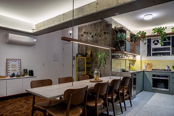 Bếp và phòng khách được tích hợp nhờ một hệ bàn được xây bằng bê tông cốt thép. Khu vực này có hình chữ L, cao 90 cm, có bếp nấu, bồn rửa. Tại nơi giao nhau với phòng khách, chiều cao hạ xuống 15 cm để trở thành bàn ăn kéo dài 3 m.