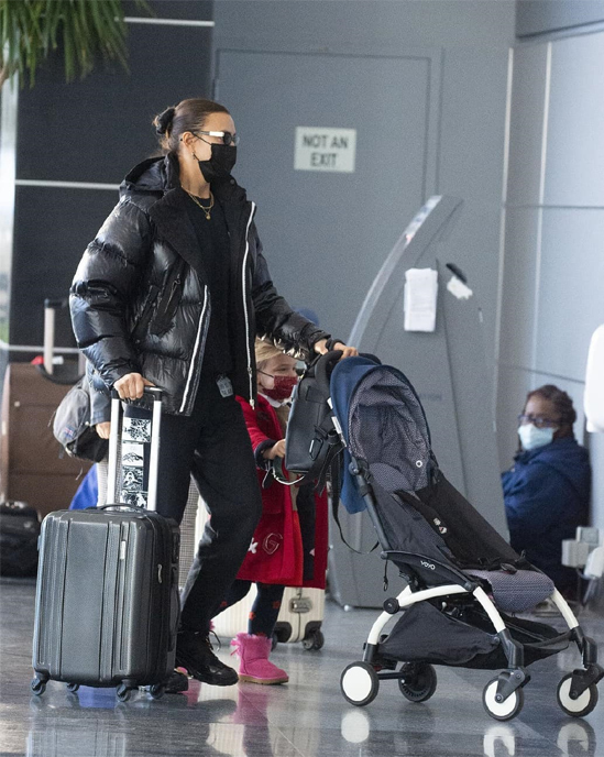 Hai mẹ con đeo khẩu trang tại sân bay, chuẩn bị cho hành trình dài tới Malibu.