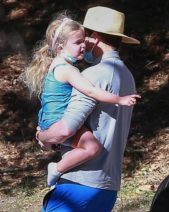 Bradley Cooper bế con gái từ xe ôtô vào nhà người bạn. Hai cha con đeo khẩu trang y tế tránh dịch.
