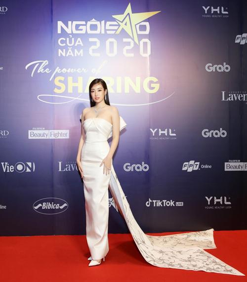 Đỗ Mỹ Linh chọn váy dạ hội tông trắng thanh nhã khi tham dự sự kiện quy tụ hơn 100 khách mời. Trên dáng váy ôm khít eo, nhà thiết kế tô điểm thâm phần nơ và đuôi váy đính kết công phu.