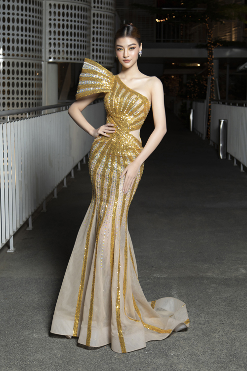 Kiều Loan diện trang phục ánh kim tông vàng gold có độ bắt sáng cao, trang phục của Nguyễn Minh Tuấn còn khai thác hiệu quả đường cong của á hậu.