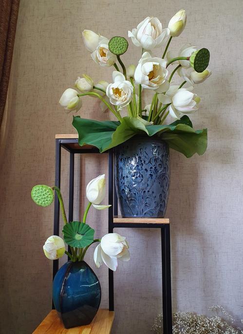 Bình hoa sen trắng trở nên ấn tượng hơn khi có thêm lá, đài sen làm nền.