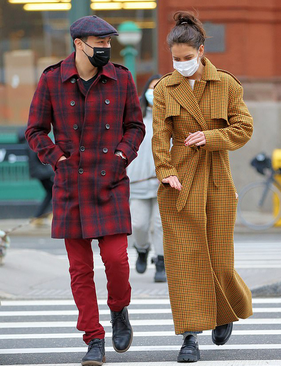 Bạn trai cô mặc áo khoác kẻ đỏ, phối đồ ăn ý với mũ nồi gần tông màu và giày đen. Chàng bếp trưởng người New York luôn ăn mặc thời thượng và chải chuốt lịch lãm mỗi khi ra đường.