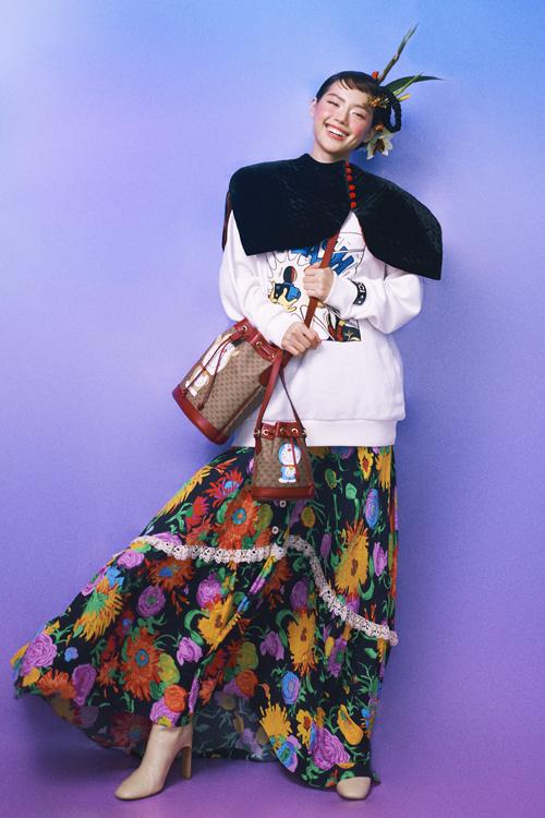 Áo choàng biến thể với phom cánh hoa làm bằng chất liệu nhung được phối cùng áo hoodie, chân váy hiện đại.