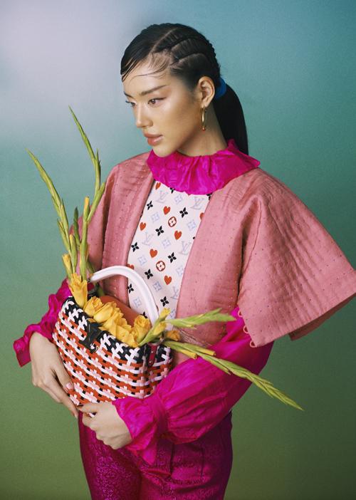 Trang phục gấm gắn liền nét vẻ đẹp Á Đông được mix ăn ý cùng áo logo của Louis Vuitton. Túi xách tay da đan cùng thương hiệu cũ được chọn sắc màu đồng điệu.
