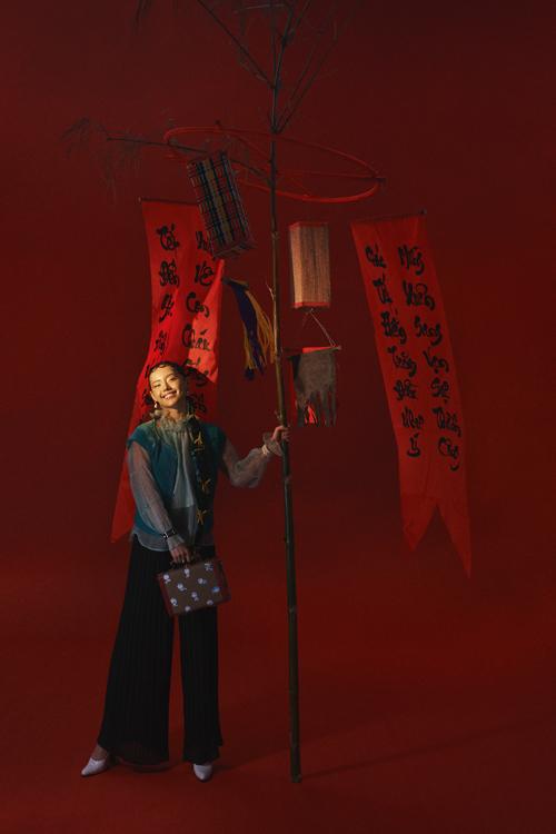 Cùng với việc chăm chút cho trang phục, những đạo cụ đậm chất Tết Việt như cây nêu, câu đối đỏ, hoa lay ơn... cũng được Khánh Linh chuẩn bị khá công phu.