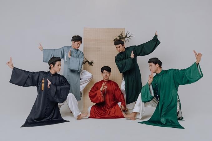 Quang Đăng mặc áo the đỏ, đội khăn xếp, nổi bật giữa dàn vũ công mặc những bộ áo dài mang gam màu lạnh.