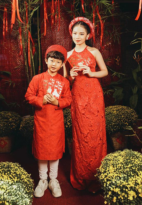 Bảo Hà diện áo dài đỏ rực tạo dáng cùng bé Nhật Huy 8 tuổi trong khung cảnh đậm sắc xuân. Bộ ảnh do chuyên gia trang điểm Lam Nguyen, stylist Nguyen Chu hỗ trợ thực hiện.