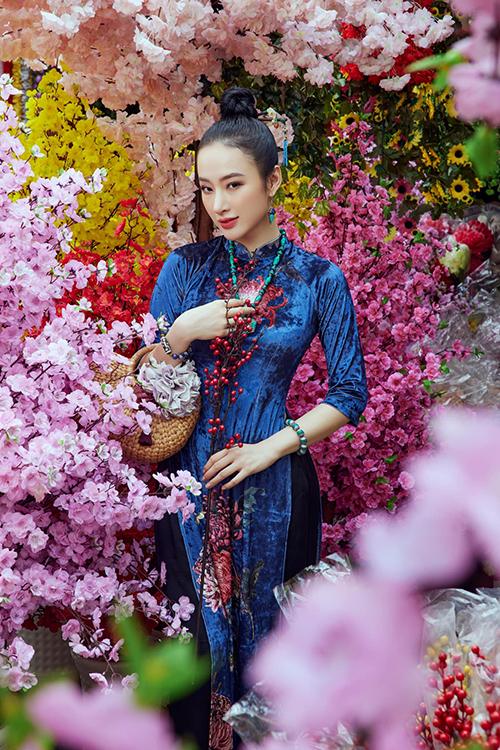 Khi diện áo nhung thêu hoa tỉ mỉ, Angela Phương Trinh chọn kiểu tóc búi gọn gàng cùng trâm cài tóc ton-sur-ton.
