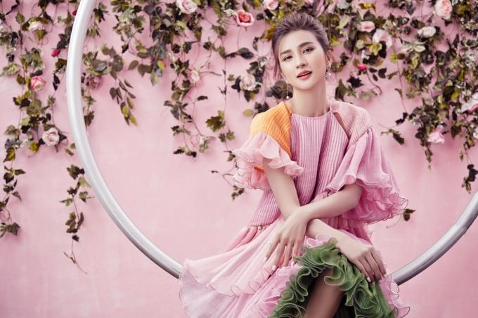 Gam màu hồng pastel nhẹ nhàng làm tăng vẻ duyên dáng. Hoa tai ngọc trai tạo điểm nhấn cho tổng thể.