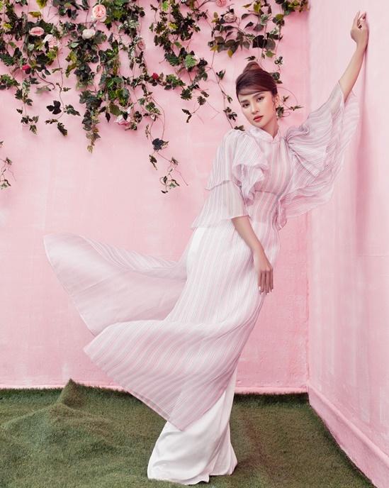 Lấy kiểu dáng từ áo dài, bộ trang phục cách tân với chi tiết tay phồng, họa tiết sọc dọc.