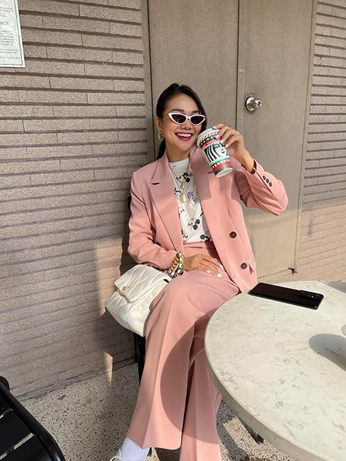 Bộ suit kết hợp giữa áo blazer cùng quần suông ống rộng gam hồng patel được Thanh Hằng phối nhịp nhàng cùng loạt phụ kiện tông trắng. Set đồ mang lại sự trẻ trung cho siêu mẫu khi đi chơi Tết cùng bạn bè.