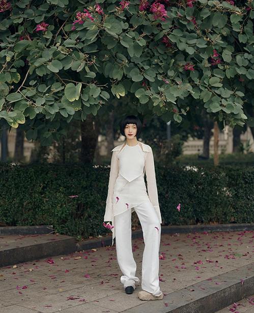 Châu Bùi thể hiện sự phá cách khi chọn áo yếm để phối đồ ton-sur-ton cùng áo áo khoác mỏng, quần suông kèm chân váy vạt xéo.