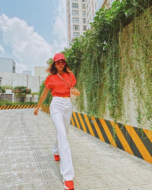 Hoa hậu HHen Niê nổi bật với cách mix áo thun đồng điệu tông cam với giày thể thao.