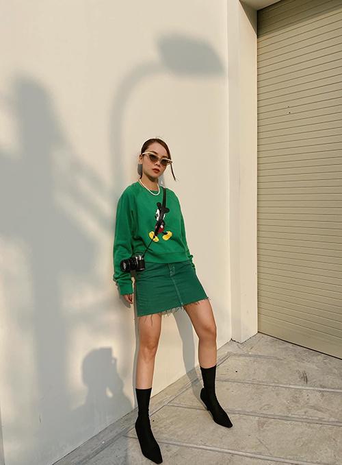 Yến Trang khoe dáng trên phối với set đồ mang thông điệp năm mới tươi xanh. Áo áo hoodie in hoạ tiết chuột Mickey được phối đồng điệu cùng chân váy jeans, phụ kiện đi kèm là bốt ôm sát cổ chân.
