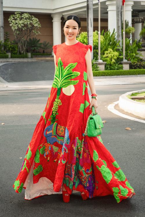 Váy dạo phố với điểm nhấn bắt mắt từ tông đỏ tượng trưng cho máy. Họa tiết rực rỡ sắc màu được trang trí hình ảnh cây cau, lá trầu và đàn trâu mang thông điệp bình yên và no ấm cho năm mới.
