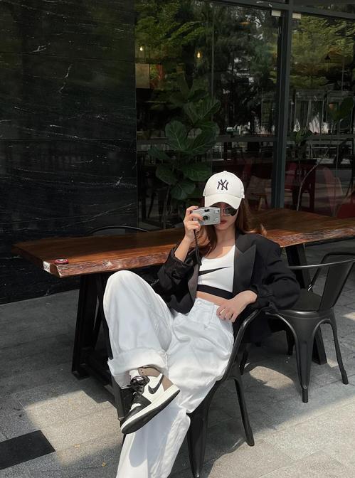 Set đồ trắng đen đơn giản nhưng vẫn giúp người mặc toát lên nét khỏe khoắn và hiện đại. Áo hở eo và giày thể thao được chọn làm điểm nhấn cho tổng thể.