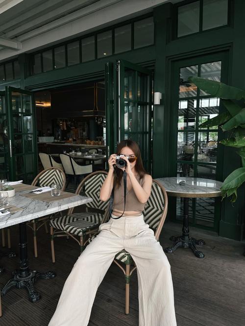 Set đồ phù hợp để đi cafe cùng bạn bè vào mùa nắng phương Nam. Áo hở eo trang trí dây đạn được Yến Trang phối ăn ý cùng quần suông ống rộng.