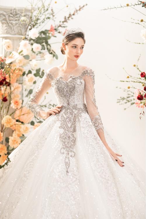 Chiếc váy phồng xòe được dựng gọng corset thu nhỏ eo, làm mới với các hoạ tiết hoa văn được phác hoạ trên bề mặt váy bằng đá pha lê.