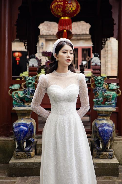 Tấm áo dài trắng tinh được lấy cảm hứng Tây phương, có độ ôm và tay, cổ xuyên thấu mờ giúp cô dâu gợi cảm trong ngày cưới.