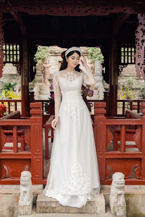 Váy cưới có cổ illusion được đắp ren dọc thân, giúp cơ thể thon gọn, mảnh mai.