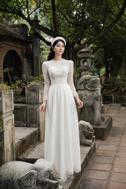 Bộ áo dài được tập trung đính kết nơi thân trên, phần tà bên dưới như mô phỏng dáng váy chữ A.