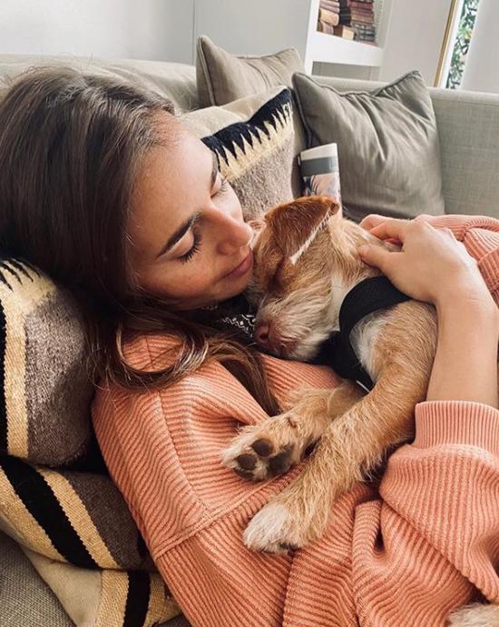 Lily ôm chú chó cưng ngủ trên sofa êm ái.