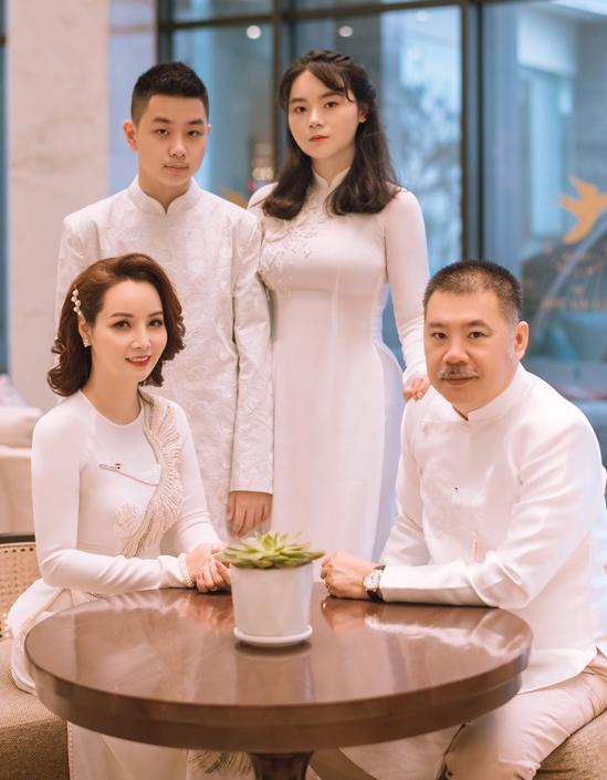 Gia đình nữ diễn viên diện áo dài trắng đồng điệu chụp ảnh kỷ niệm.